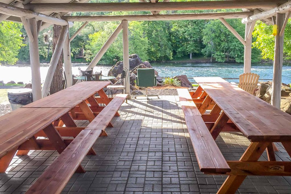 redwood picnic tables under canopy at campground