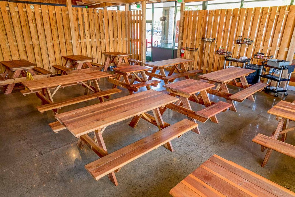Redwood picnic tables inside burger restaurant