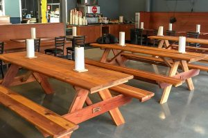 redwood picnic tables indoors in eatery
