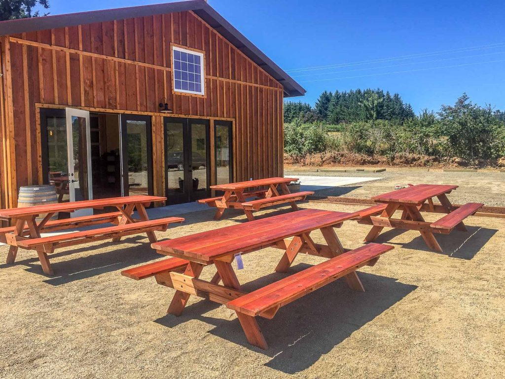 Standard redwood tables with attached benches, outside a winery