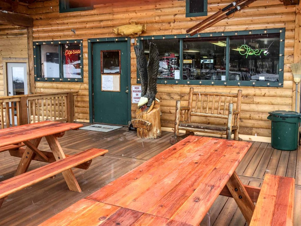 Standard redwood tables with attached benches, outside a mountain lodge